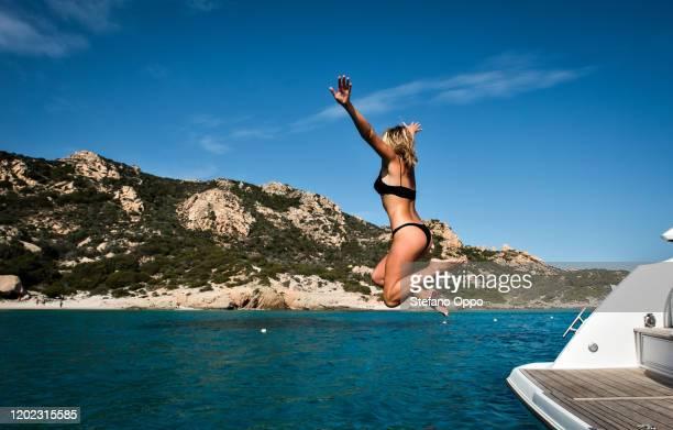 woman jumping into sea from yacht, la maddalena island, sardegna, italy - cerdeña fotografías e imágenes de stock
