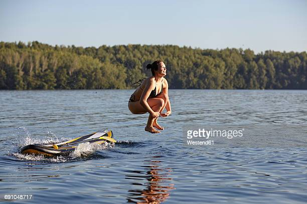 woman jumping into water from paddleboard - cannon stock pictures, royalty-free photos & images
