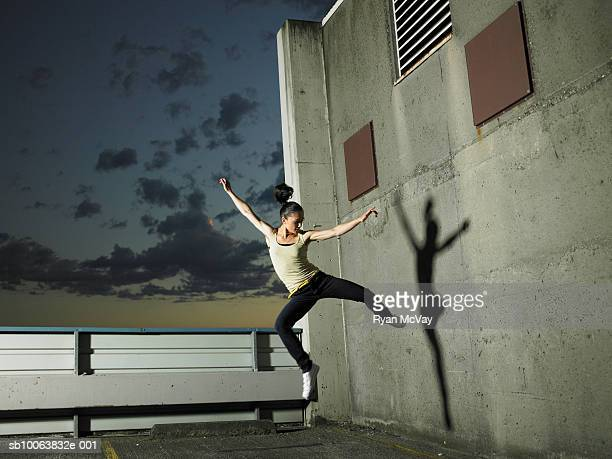 Woman jumping mid air on rooftop carpark