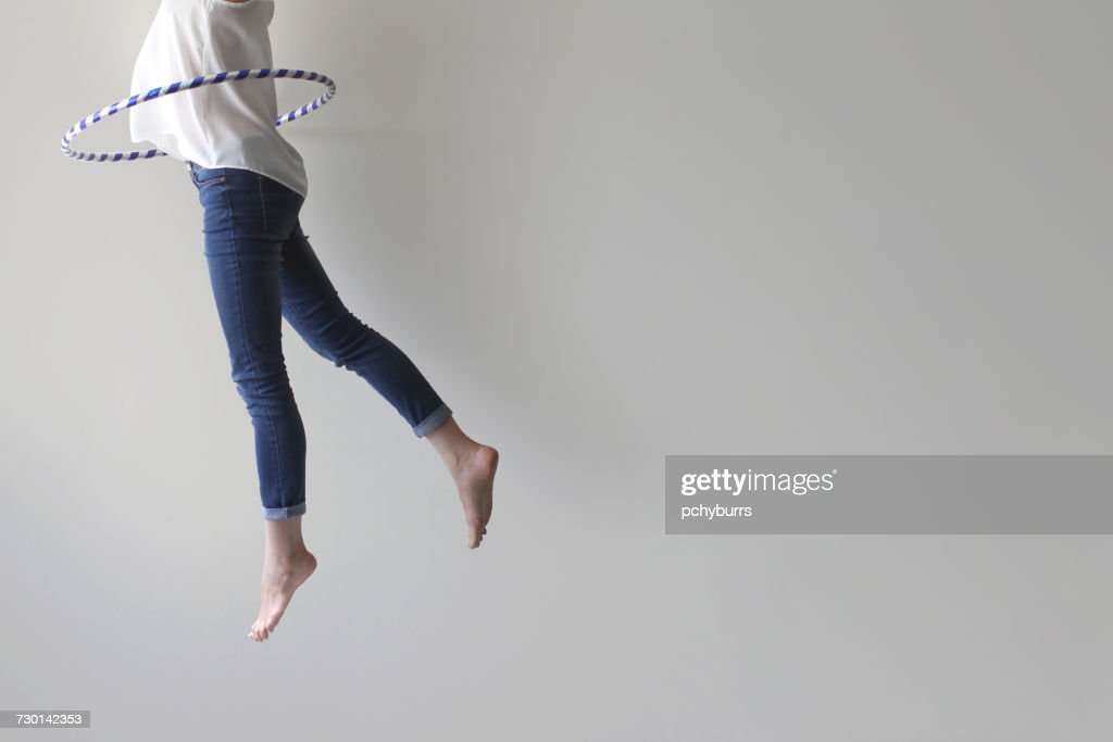 Woman jumping mid air with plastic hoop round her waist : Stock Photo