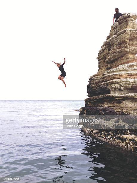 Woman jumping off rocks into the ocean