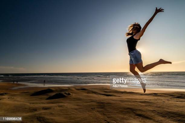 woman jumping on a beach at sunset. - august stock pictures, royalty-free photos & images