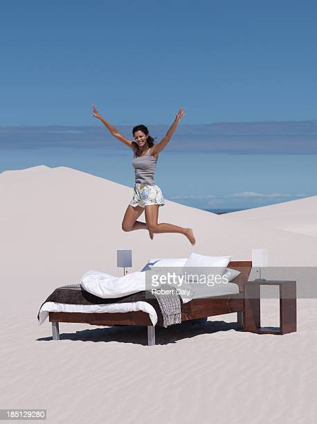 A woman jumping on a bed outdoors