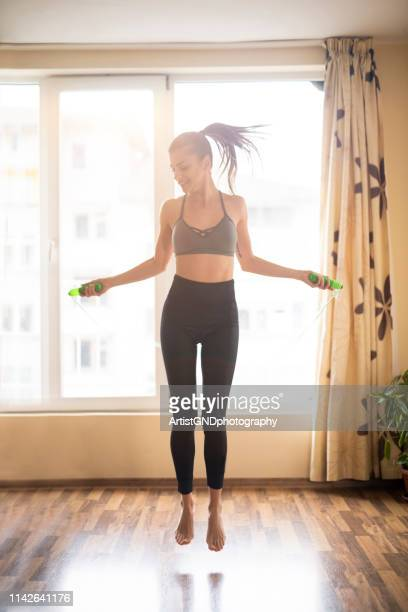 woman jumping on a rope at home. - cardiovascular exercise stock pictures, royalty-free photos & images