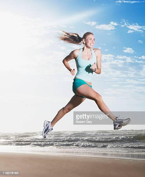 mulher saltar na praia - adulto de idade mediana imagens e fotografias de stock