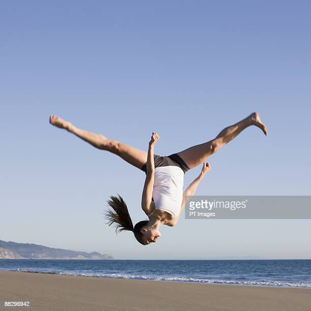 woman jumping on beach - acrobatic activity stock pictures, royalty-free photos & images