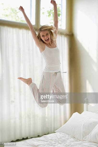 Woman jumping on bed