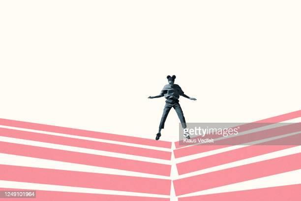 woman jumping on broken pink block stacks - バイアス ストックフォトと画像
