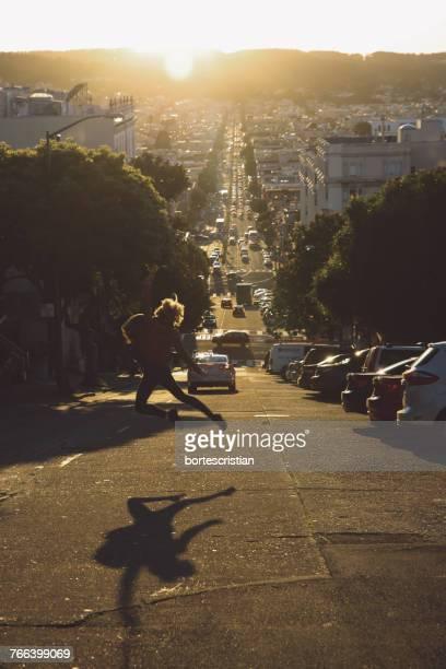 woman jumping on city street against sky during sunset - bortes stock-fotos und bilder