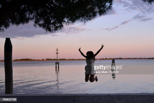 woman jumping on sand against sea at beach - muro stock photos and pictures
