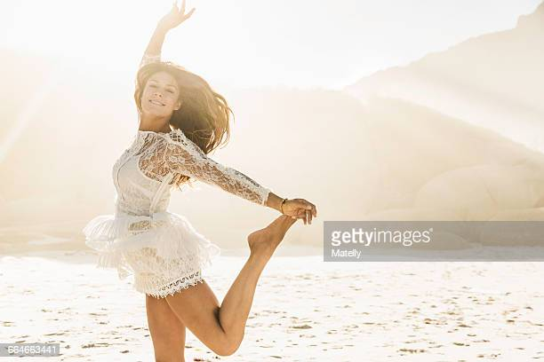 Woman jumping on sunlit beach, Cape Town, South Africa