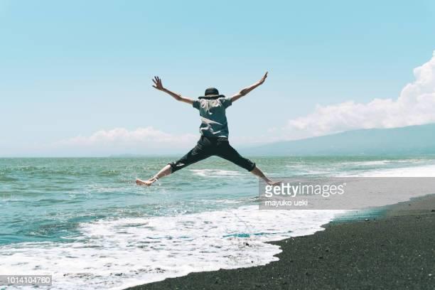 uma mulher pulando na praia - ditador - fotografias e filmes do acervo