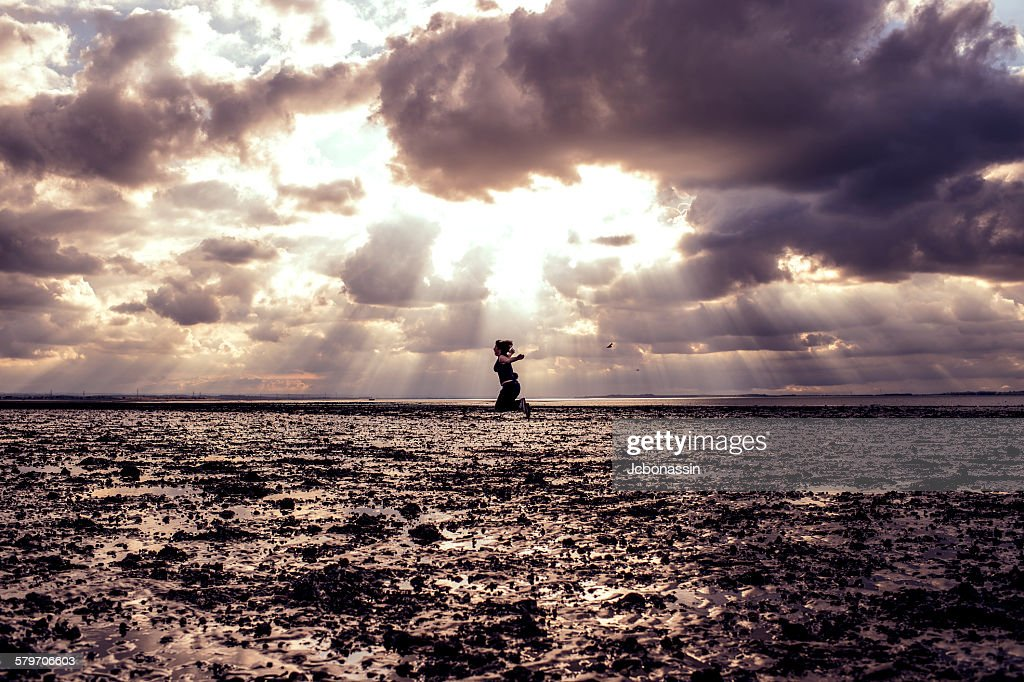 Woman jumping on the beach : Stock Photo