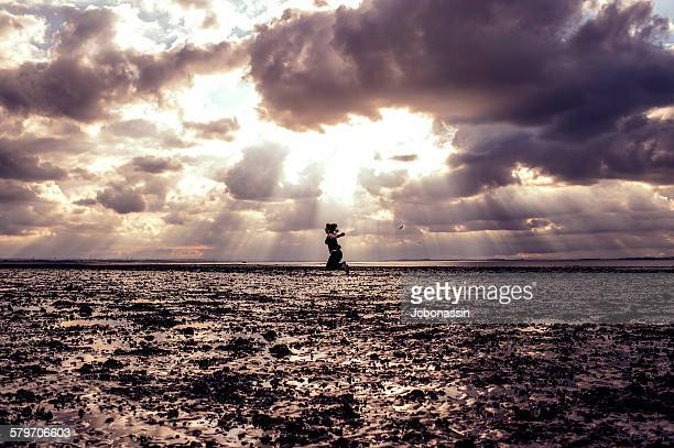 woman jumping on the beach - jcbonassin stock pictures, royalty-free photos & images