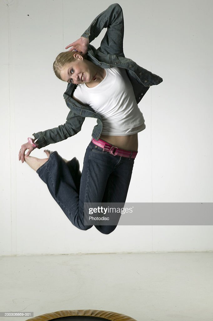 Woman jumping on trampoline in studio : Stock Photo