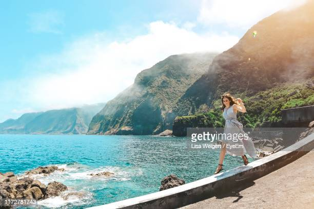 woman jumping on wall over sea against sky - ilha da madeira imagens e fotografias de stock
