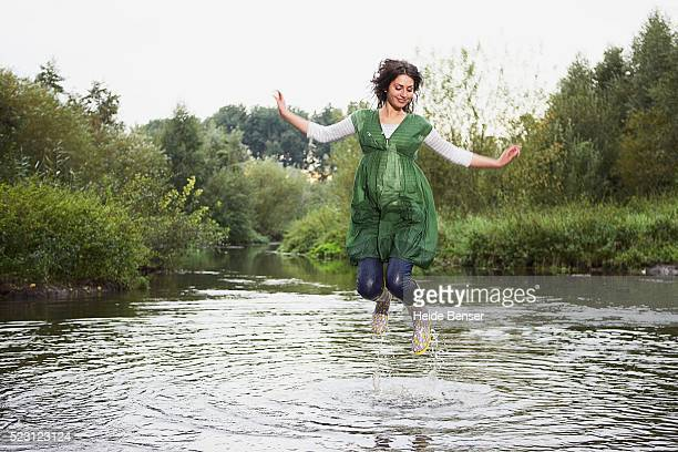 woman jumping out of a river - wet jeans stock photos and pictures