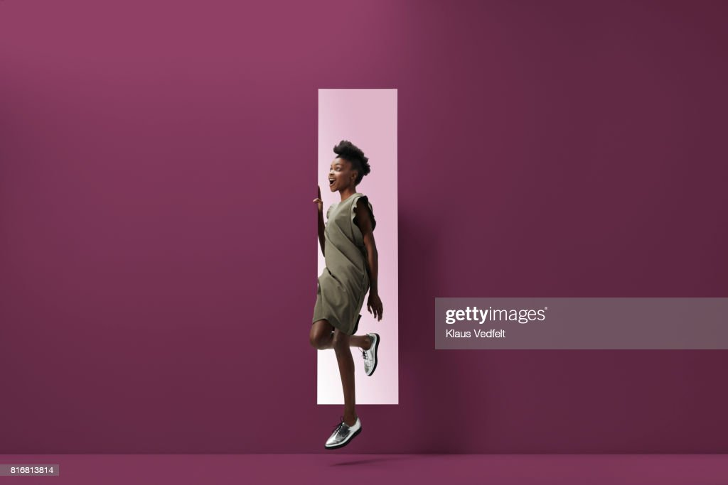 Woman jumping out of rectangular opening of coloured wall : Foto stock