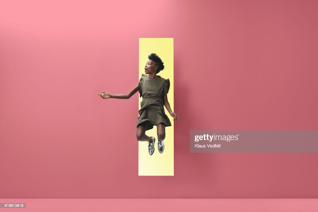 Woman jumping out of rectangular opening of coloured wall : Stock Photo