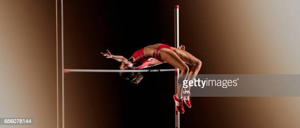 woman jumping over a horizontal bar during high jump - high jump stock pictures, royalty-free photos & images
