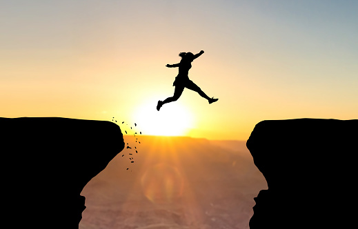 Woman jumping over abyss. 927775738