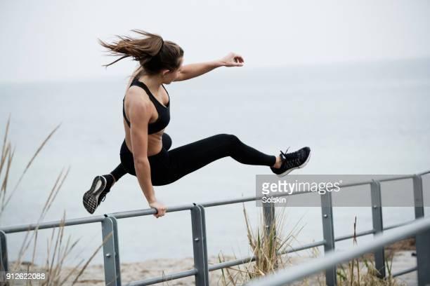 woman jumping over fence as sports exercise - valla límite fotografías e imágenes de stock