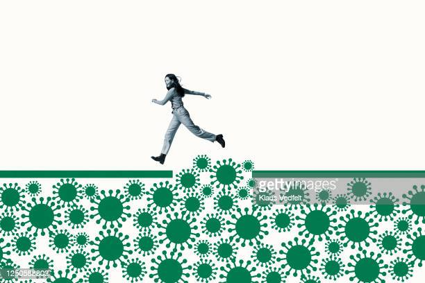 woman jumping over green coronavirus under ramp - lifestyle stock pictures, royalty-free photos & images