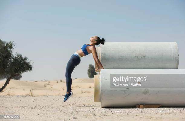 woman jumping over pipe against sky - aikāne stock pictures, royalty-free photos & images