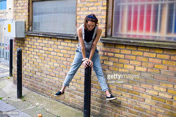 woman jumping over pole in city street - bib overalls stock pictures, royalty-free photos & images