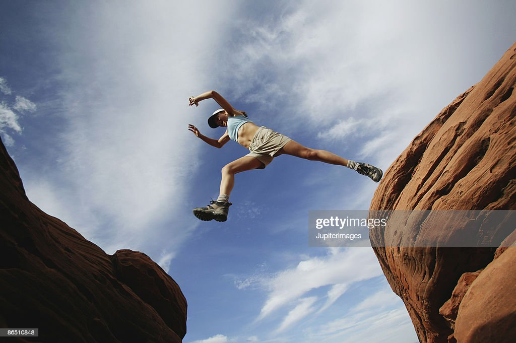 Woman jumping over rock ledge : Stock Photo