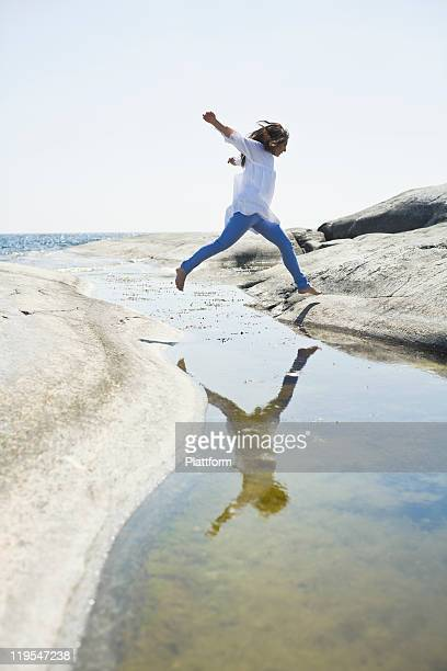 woman jumping over water to rock - one mature woman only stock pictures, royalty-free photos & images
