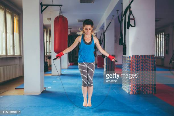 woman jumping rope in a gym - skipping along stock photos and pictures