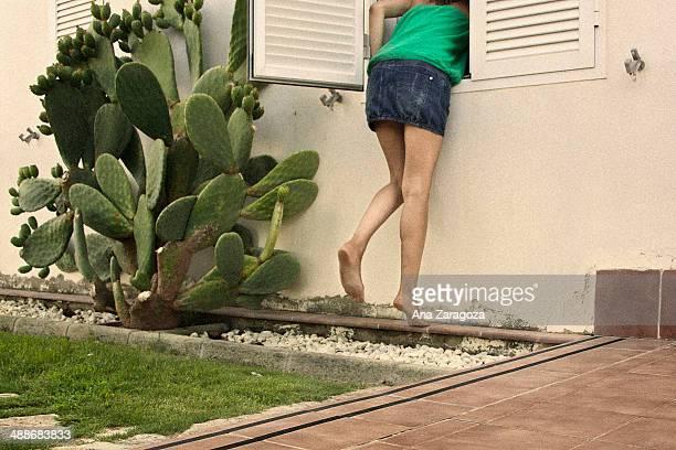 Woman jumping through a window