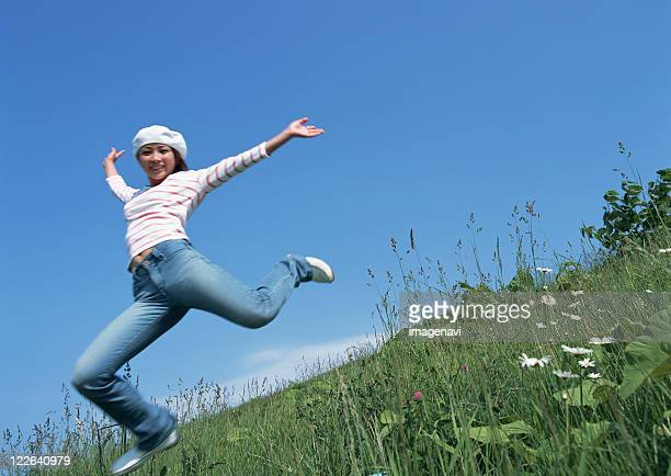 Woman jumping up in field