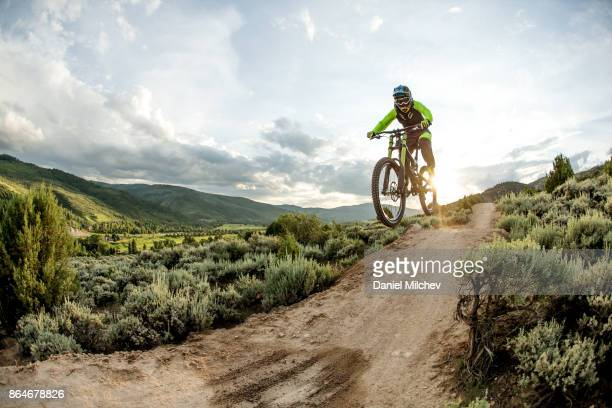 woman jumping with a mountain bike at sunset. - avon colorado stock photos and pictures