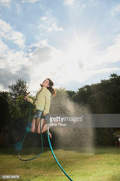 Woman Jumping with Garden Hose