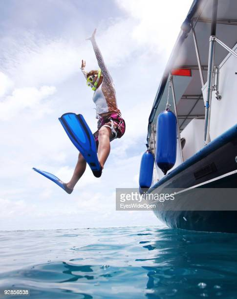 Woman jumps from a diving boat at a snorkeling trip to the reef of Addu Atoll on September 27, 2009 in Male, Maldives.The maldive islands consist of...