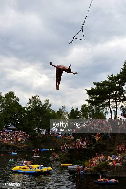 A woman jumps from a swing to the lake of the village of Hrimezdice 60 kilometers from Prague during an unofficial Czech outdoor free style jump...