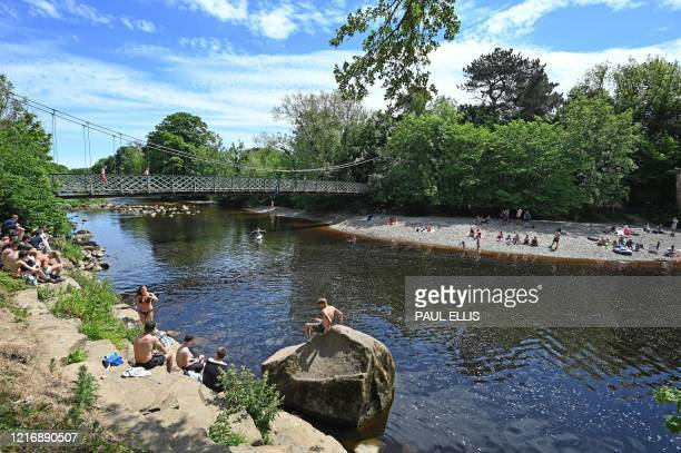 Woman jumps from the suspension bridge into the water as others relax on the banks of the River Wharfe in Ilkley, northern England, on June 2, 2020...