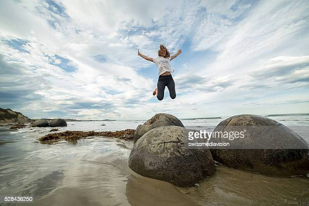 Woman jumps high in the air above spheric boulders
