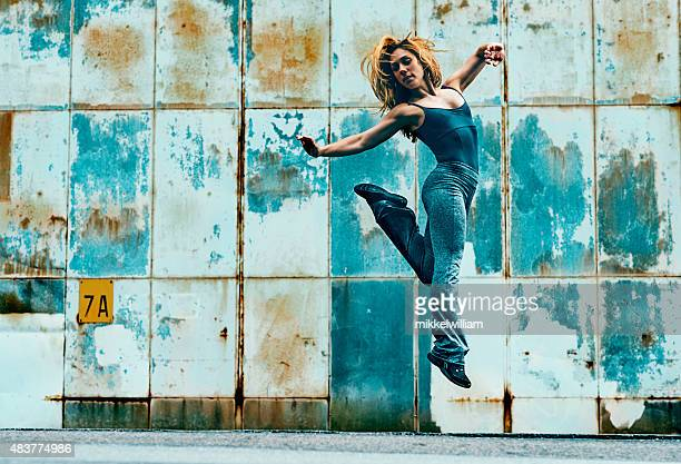 Woman jumps high into the air and makes a kick