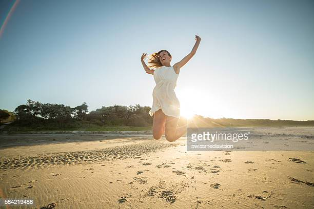Woman jumps high up in the air on beach-sunset
