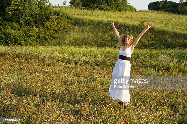 Woman jumps in a poppies field