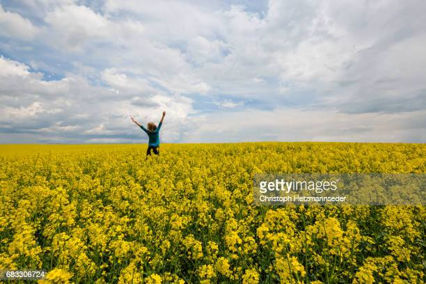 Woman jumps in canola field