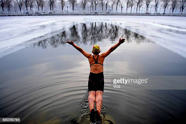 A woman jumps into a pool dug in the frozen river at Beiling Park in the smog on December 20 2016 in Shenyang Liaoning Province of China Winter...