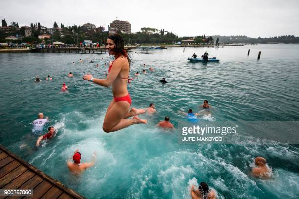 A woman jumps into the water during a traditional New Year bath in the Adriatic sea in Portoroz on January 1 2018 / AFP PHOTO / Jure Makovec
