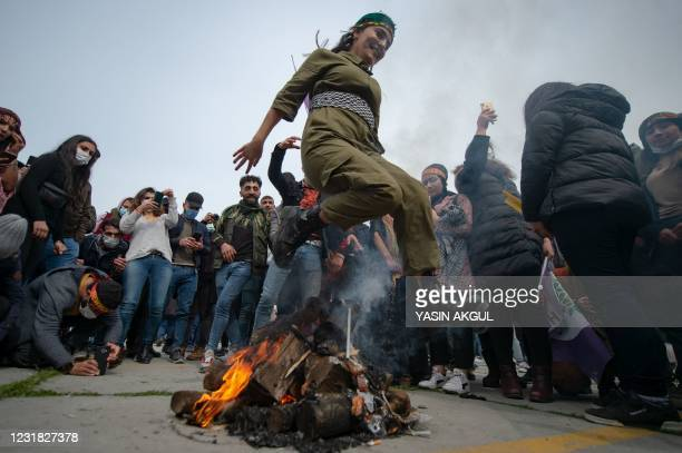 Woman jumps over a bonfire during a Kurdish celebration of Nowruz, the Persian New Year, in Istanbul on March 20, 2021.