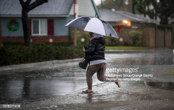 A woman jumps over flowing water along East Santa Clara Avenue in Santa Ana as heavy rainfall fell throughout Orange County on Thursday December 6...
