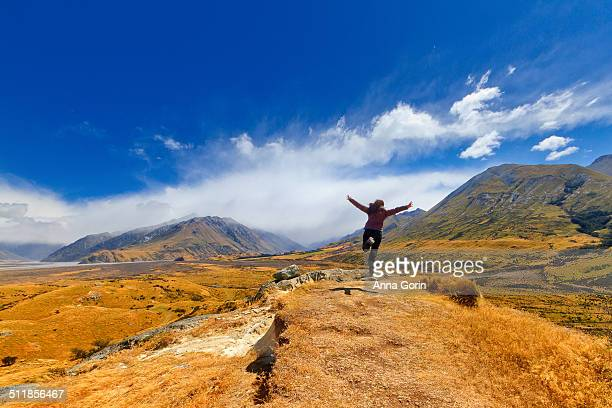 Woman jumps with arms outstretched in New Zealand
