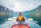 Woman kayaking in fjord in Norway.